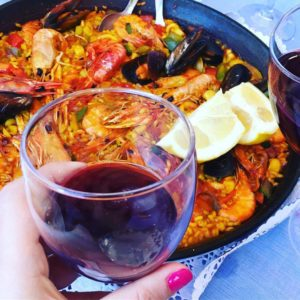 paella with a glass of red wine